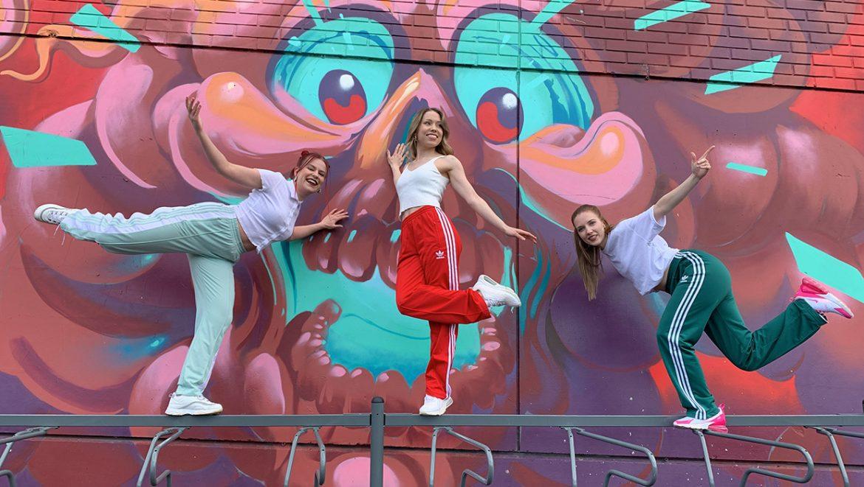 kolme tanssijaa graffitiseinää vasten